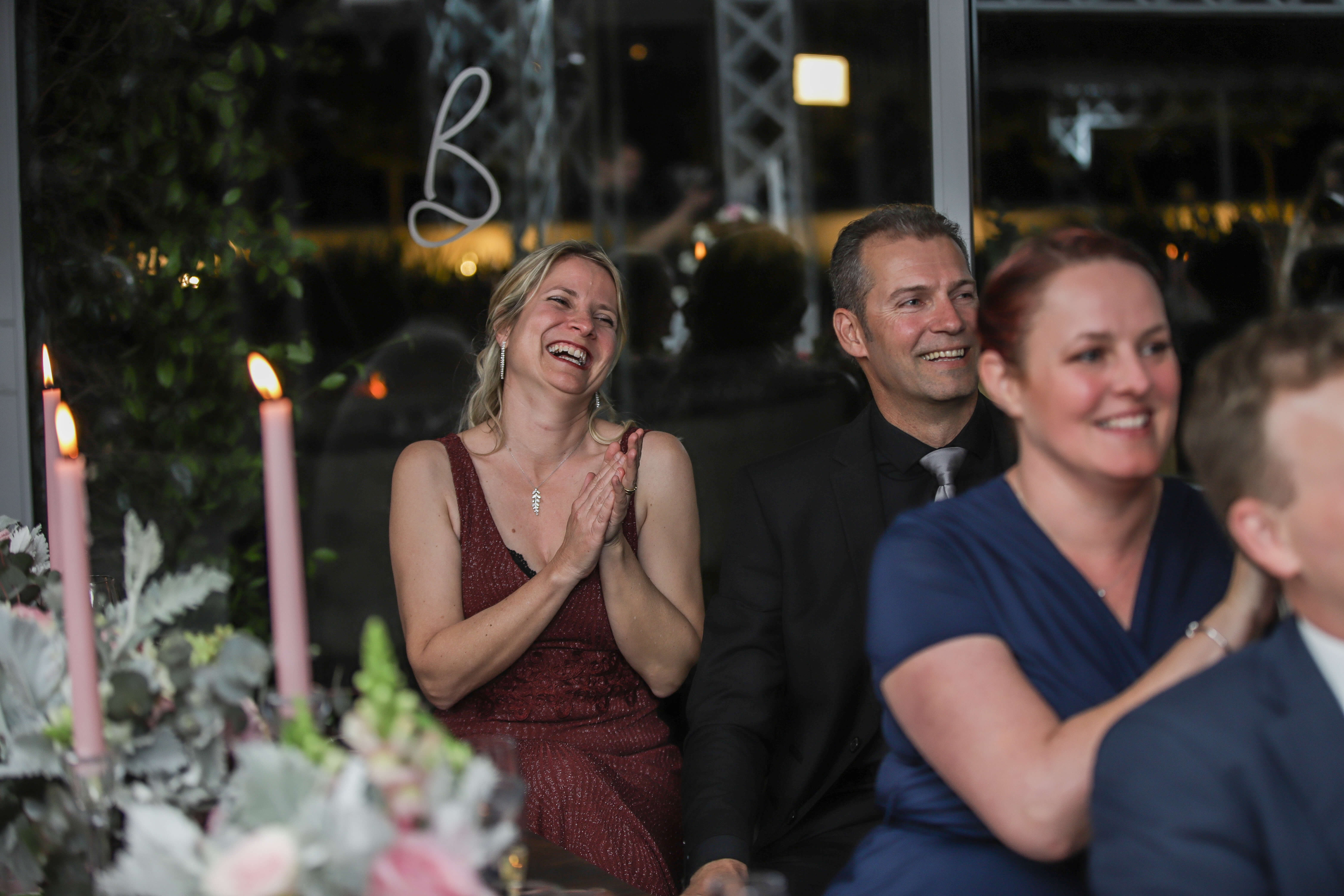 Guests clapping, smiling and laughing to a wedding speech in Stellenbosch.