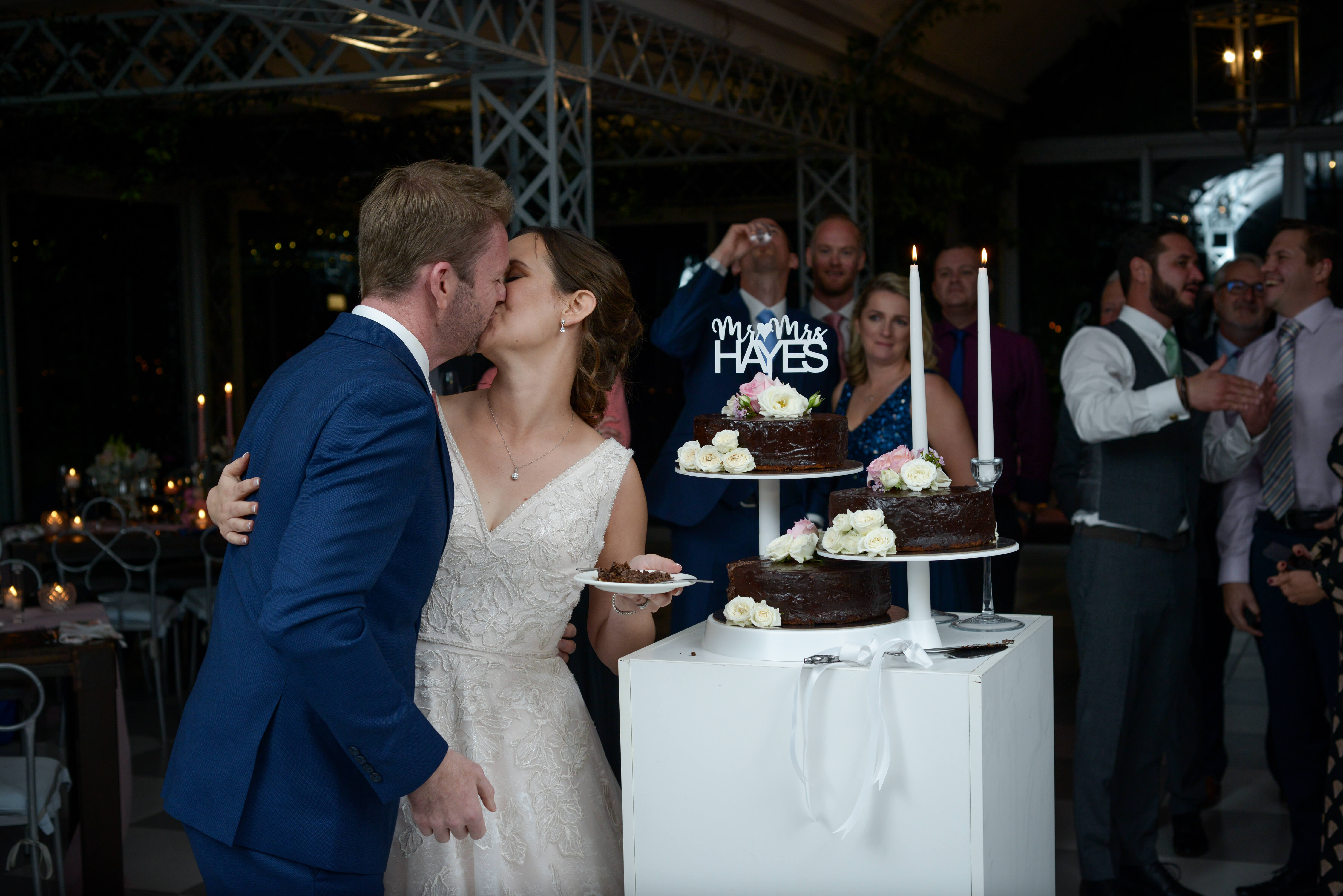 Groom and his bride kissing after cutting their wedding cake.