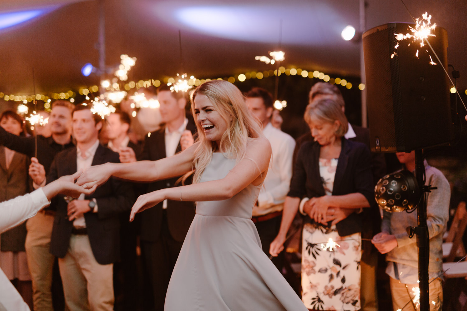 Bride dancing with friends while laughing immenesly.