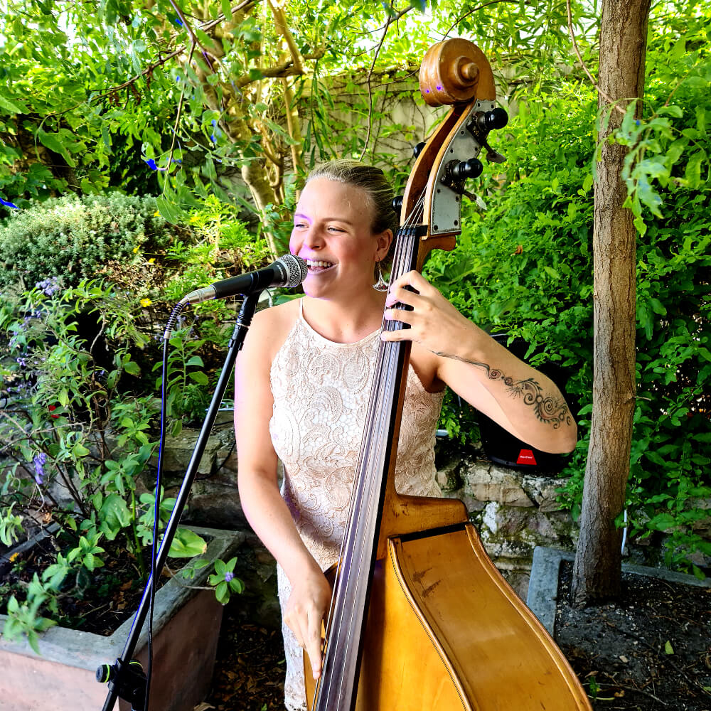 A blonde babe singing and playing the double bass in a beatiful garden scene.