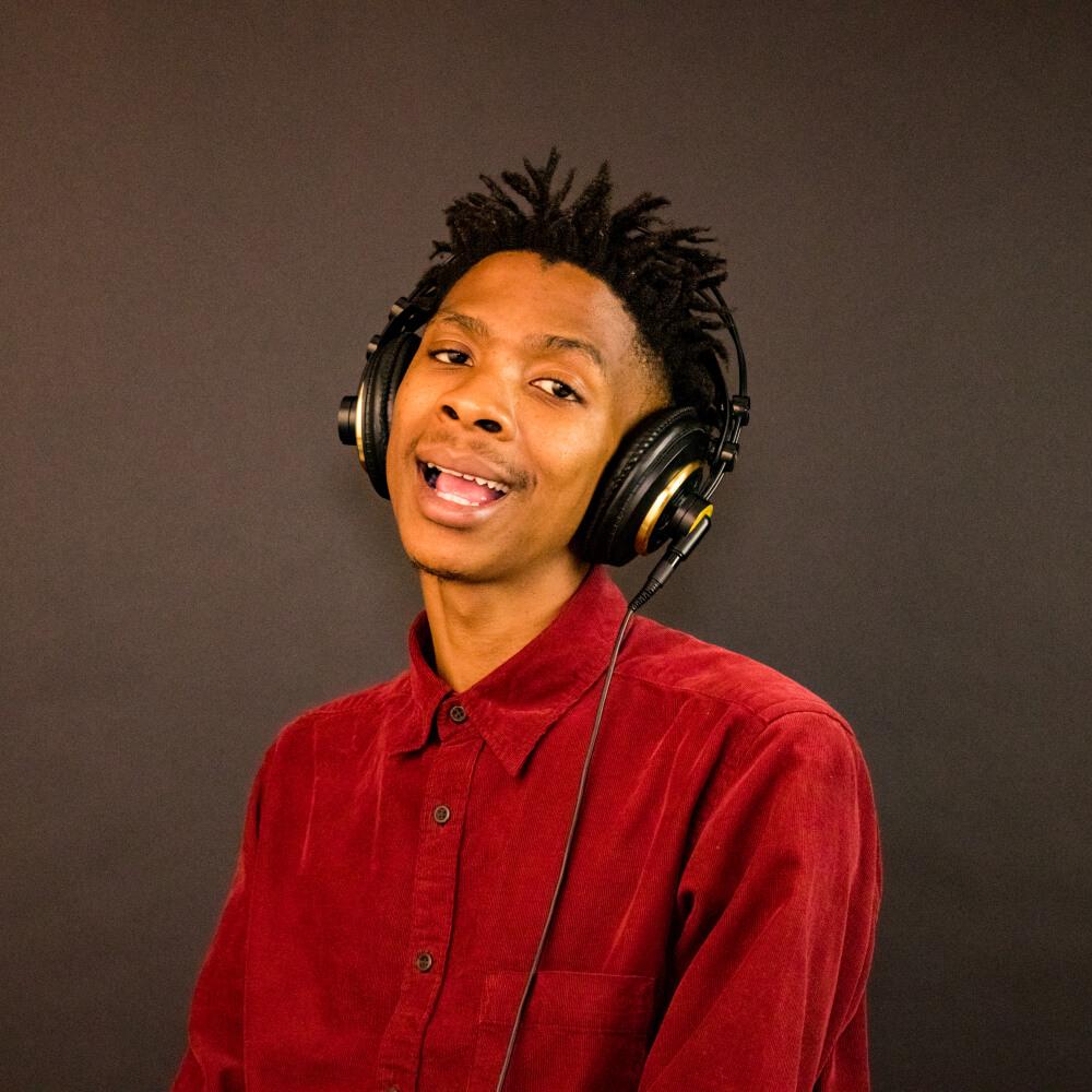 Black African soul artist, Kila G wearing headphones and smiling.