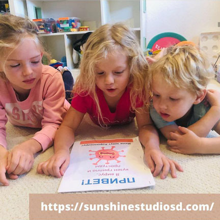 Three children reading from a flyer