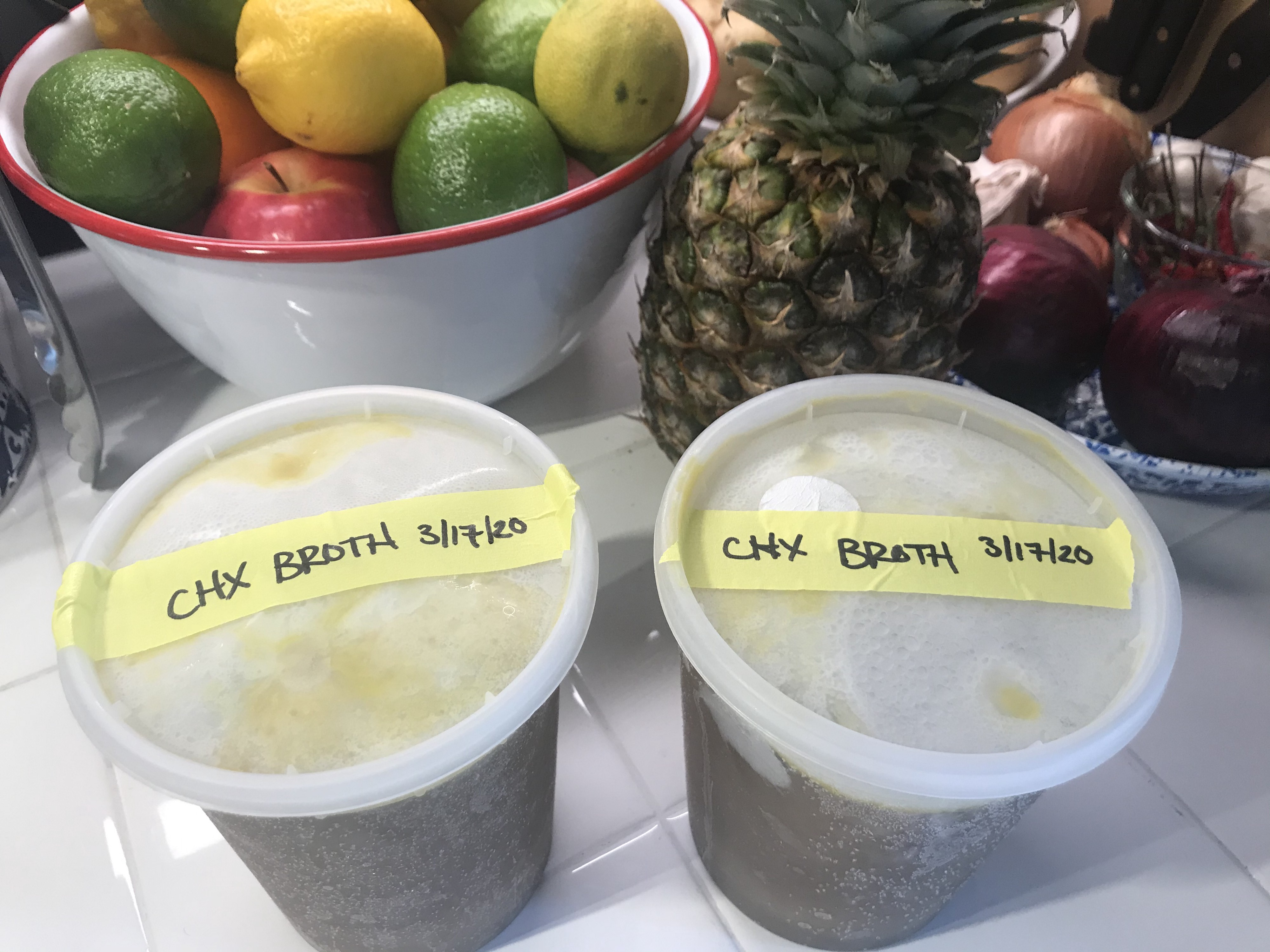 Two labeled containers of frozen chicken broth