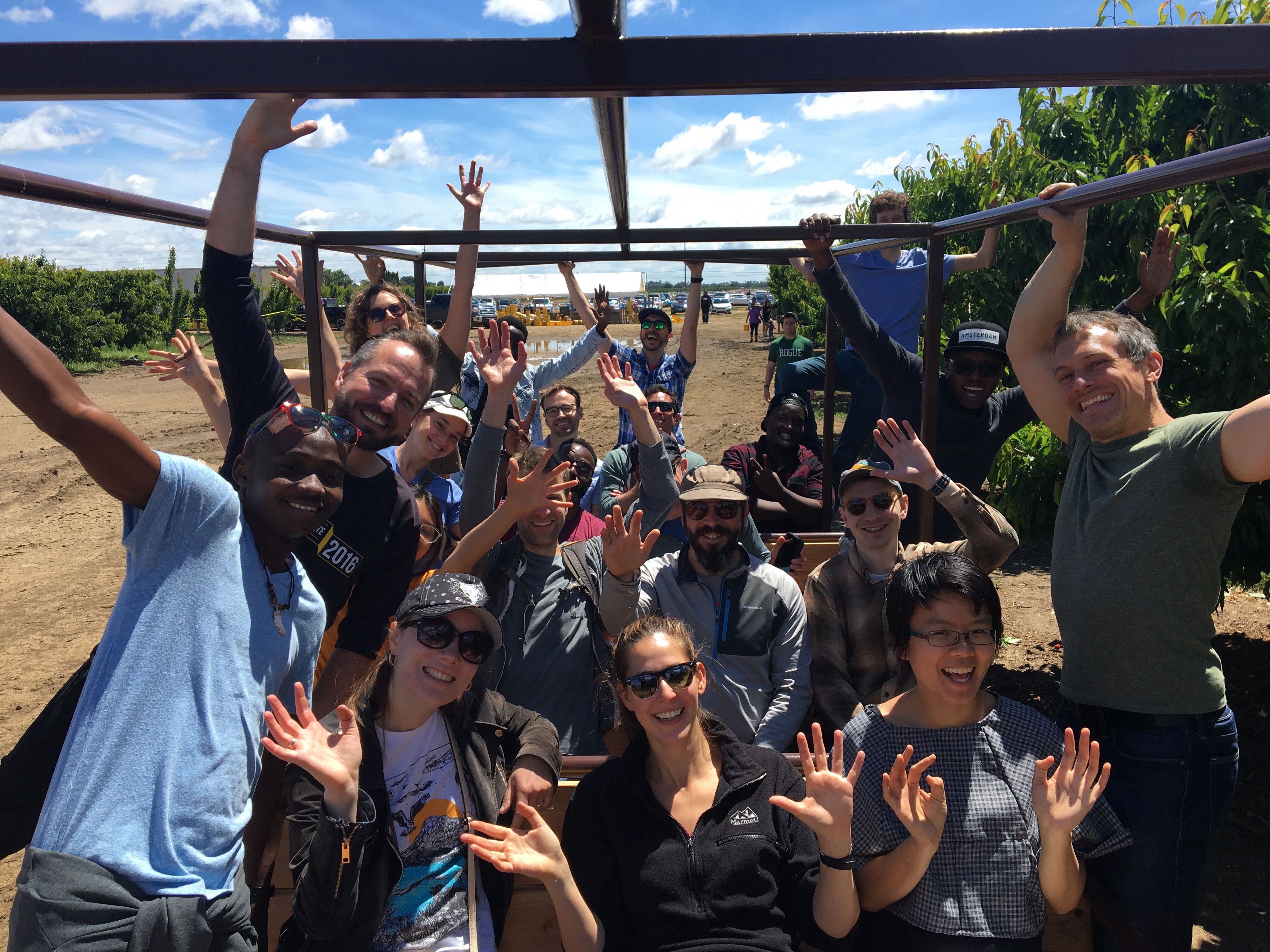 Meal Hero team waving while on a team outing to an orchard