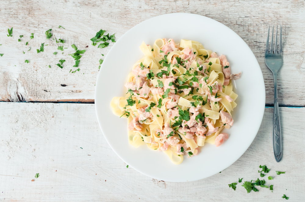 A plate of pasta with salmon on a wooden table