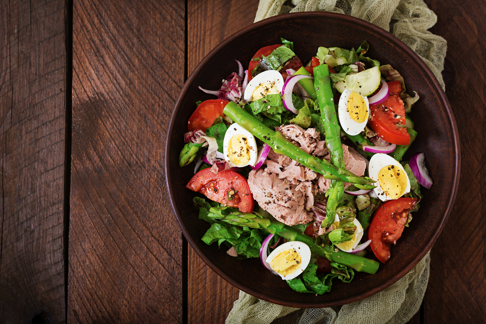 Tuna salad in a bowl with asparagus, tomatoes, and eggs