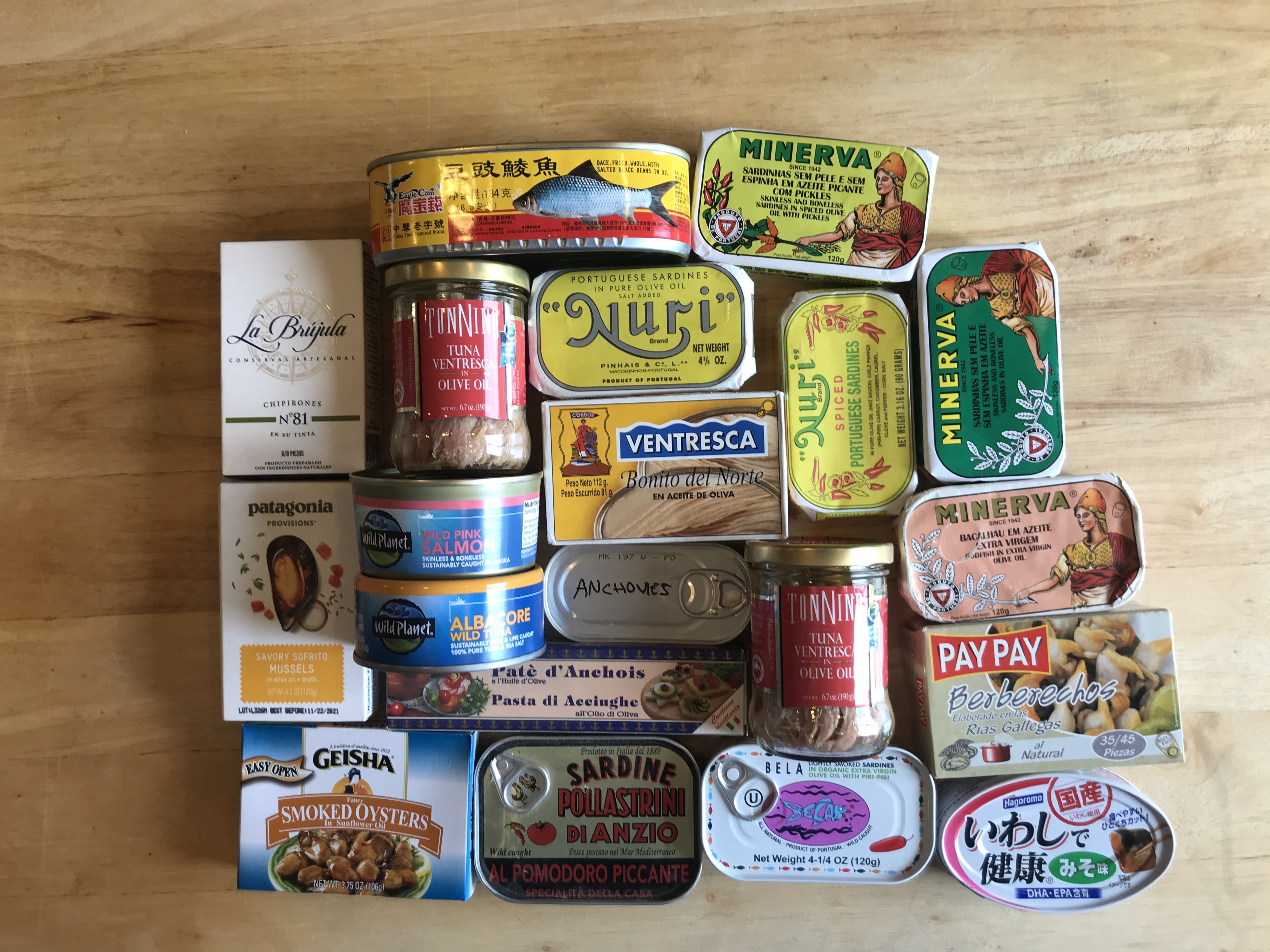 A variety of tinned fish arranged on a wooden table