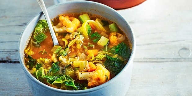 Rustic vegetable soup in a pot with a spoon