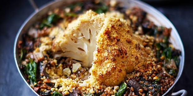Whole roasted cauliflower in an oven dish with salad