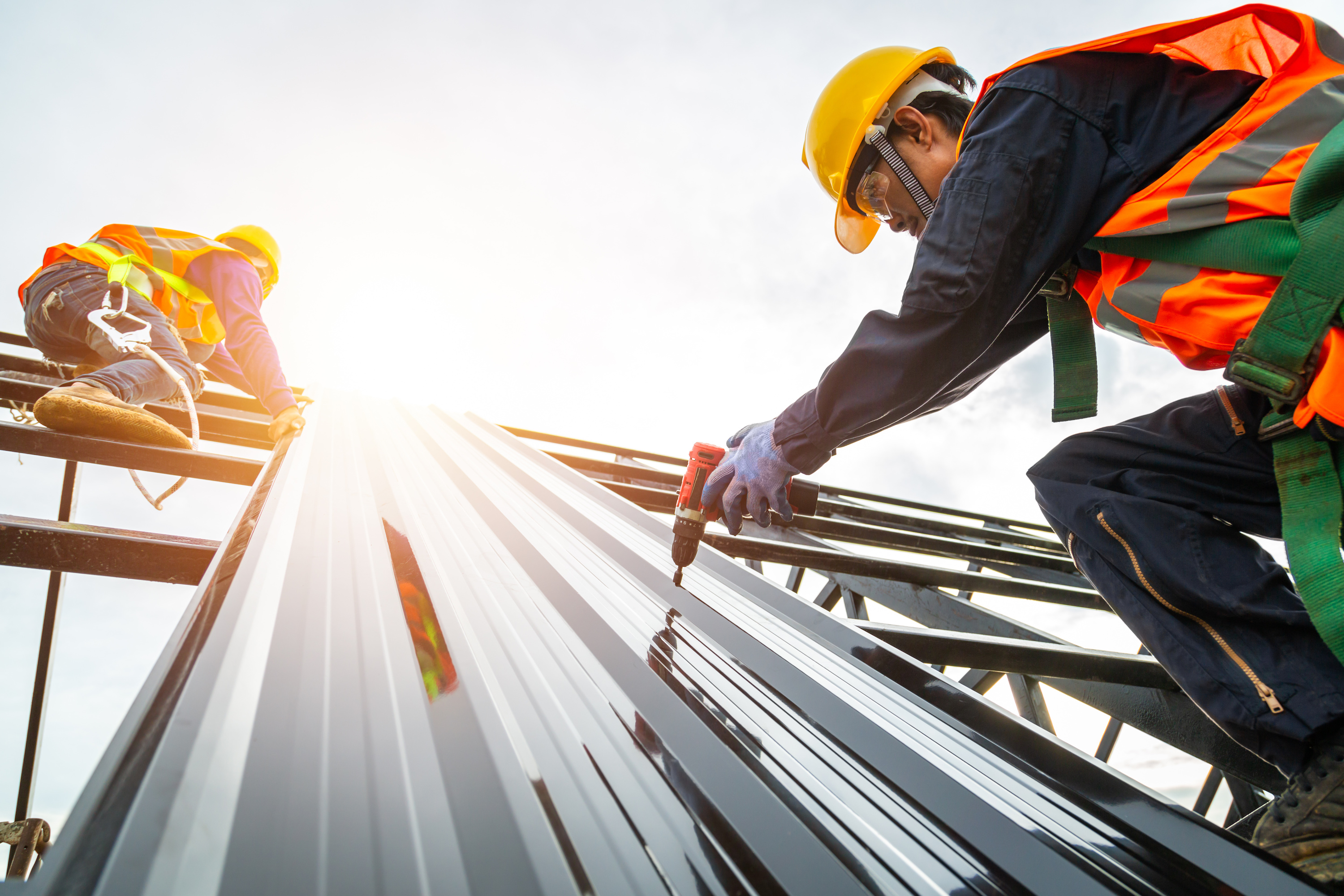 Construction workers installing roof material