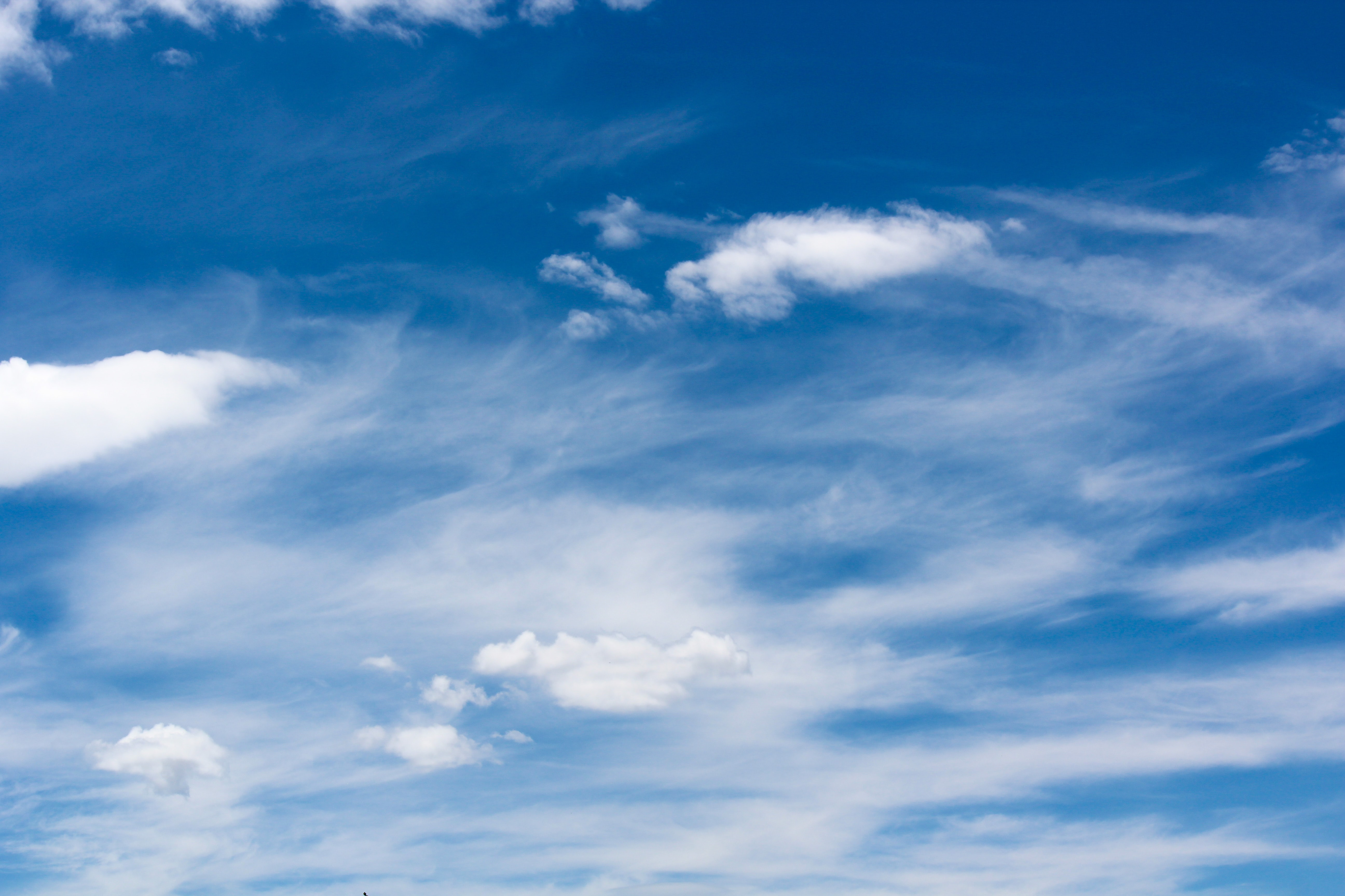 A blue sky with streaks of cirrus clouds in the background and a few puffy clouds in the foreground