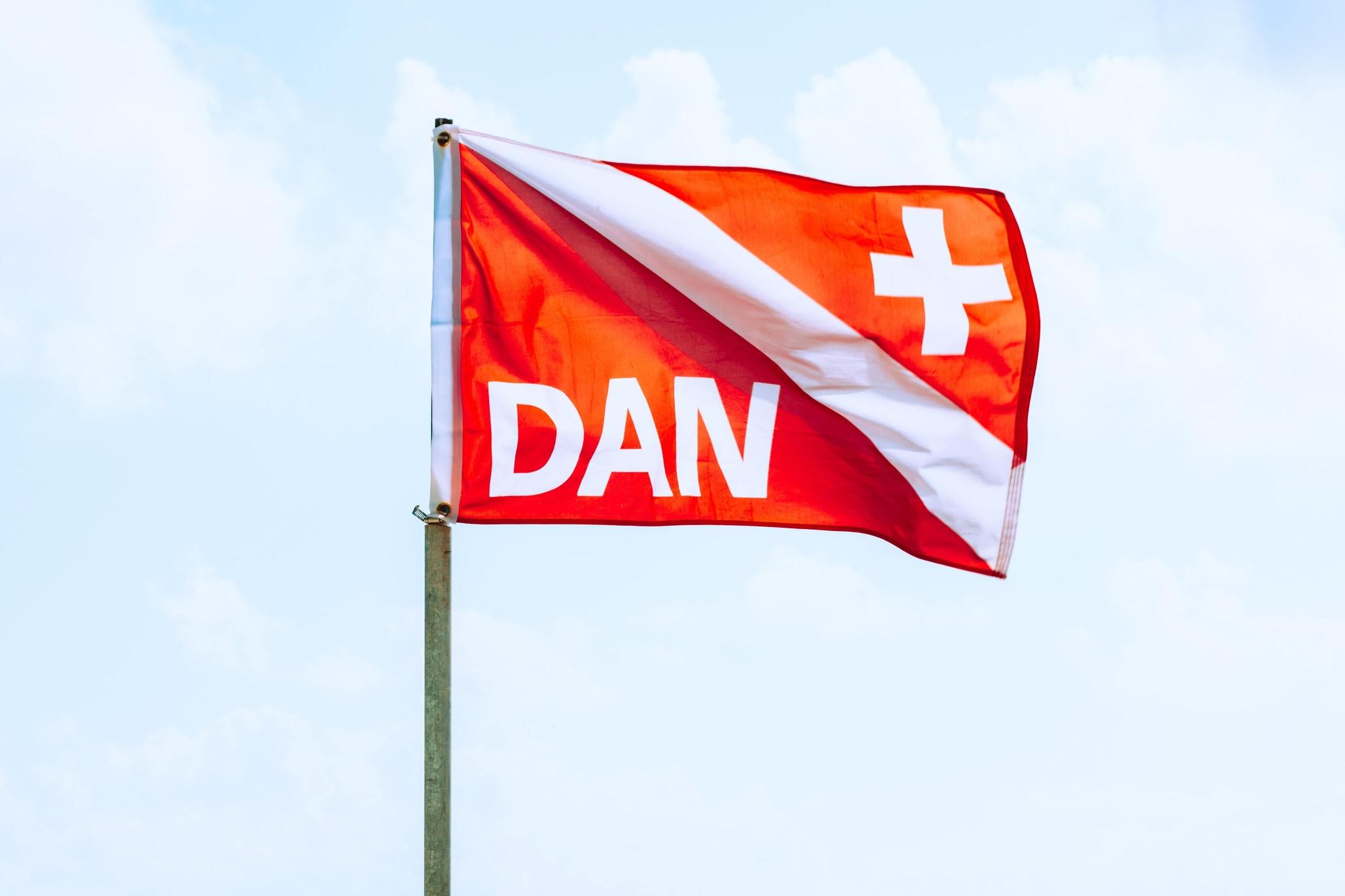 A flag of the scuba diving insurance company DAN on the beach