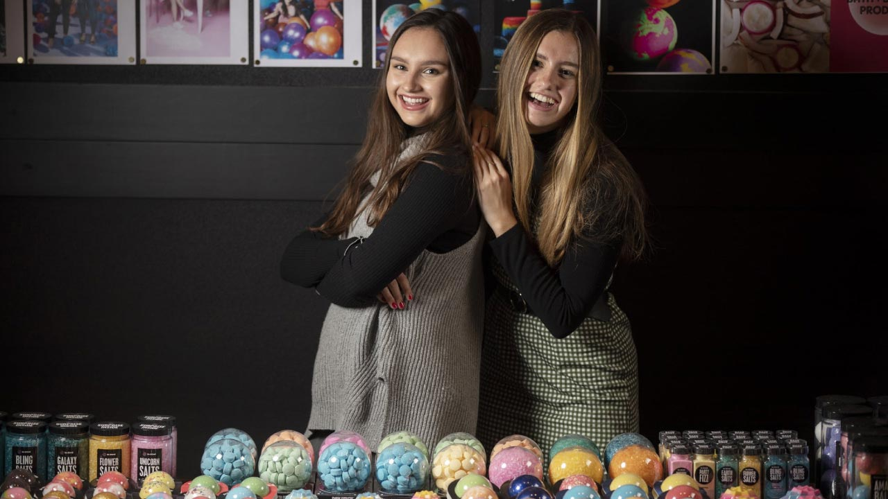 Caroline and Isabel Bercaw, founders of Da Bomb Bath Fizzers side by side with their products displayed in front of them.