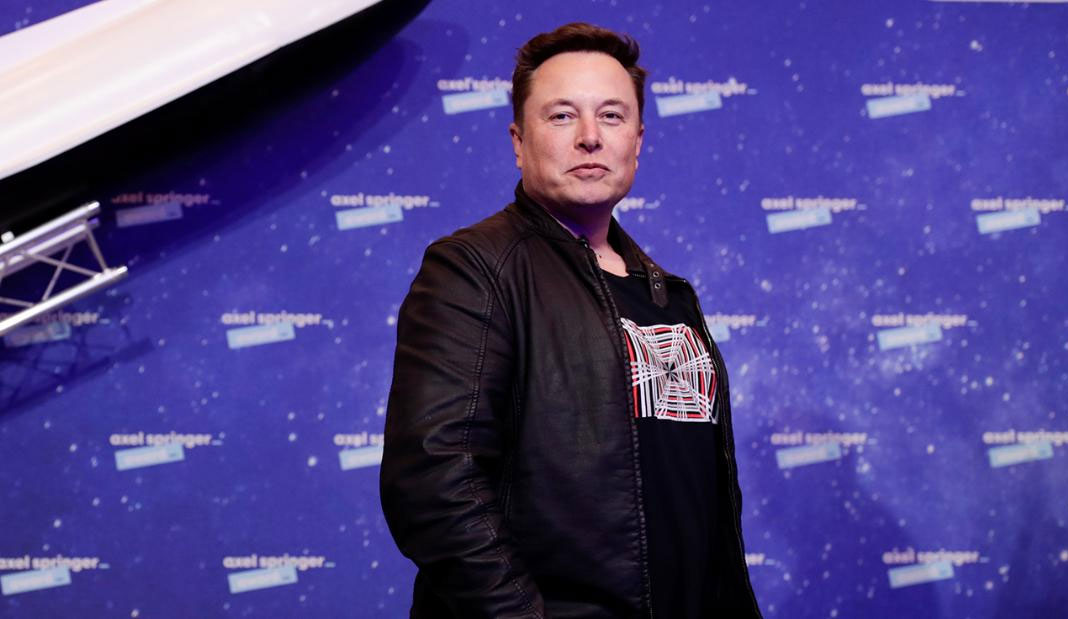 Elon Musk standing confidently, wearing black in front of a blue background.
