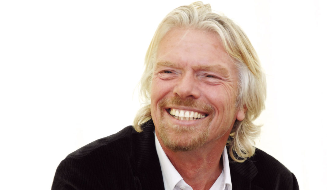 Richard Branson happily smiling wearing a suit in white background.