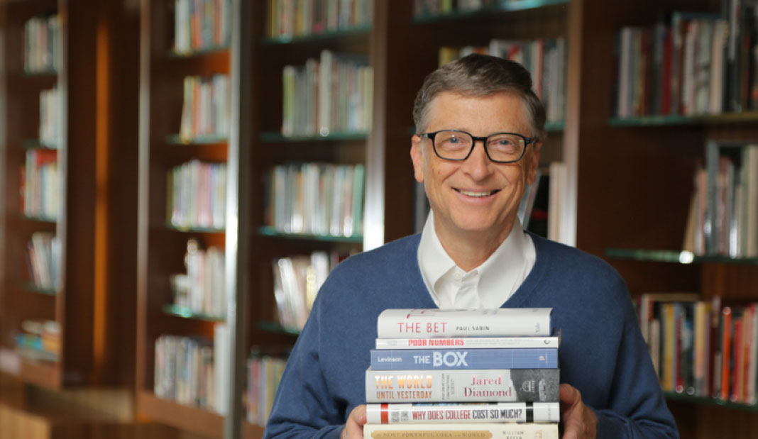Bill Gates holding his collection of favorite books while smiling at the camera.