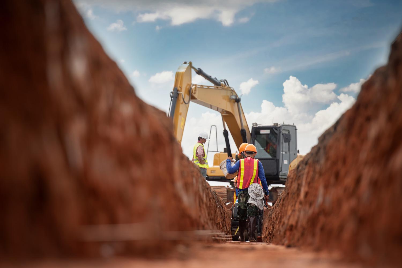 men working in safety gear near excavator