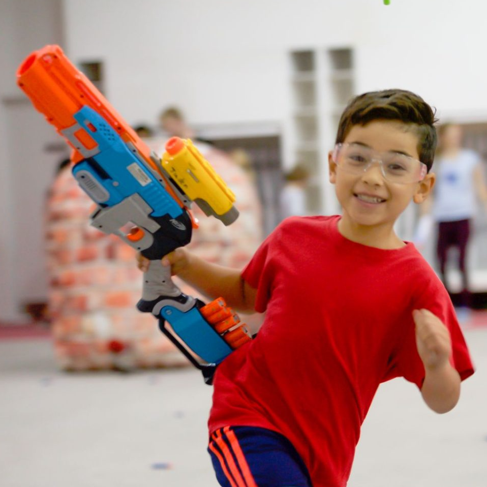 A child playing with a nerf blaster