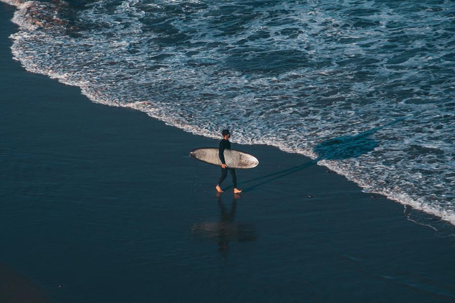 A surfer walking towards the ocean in Arrifana beach Algarve Portugal