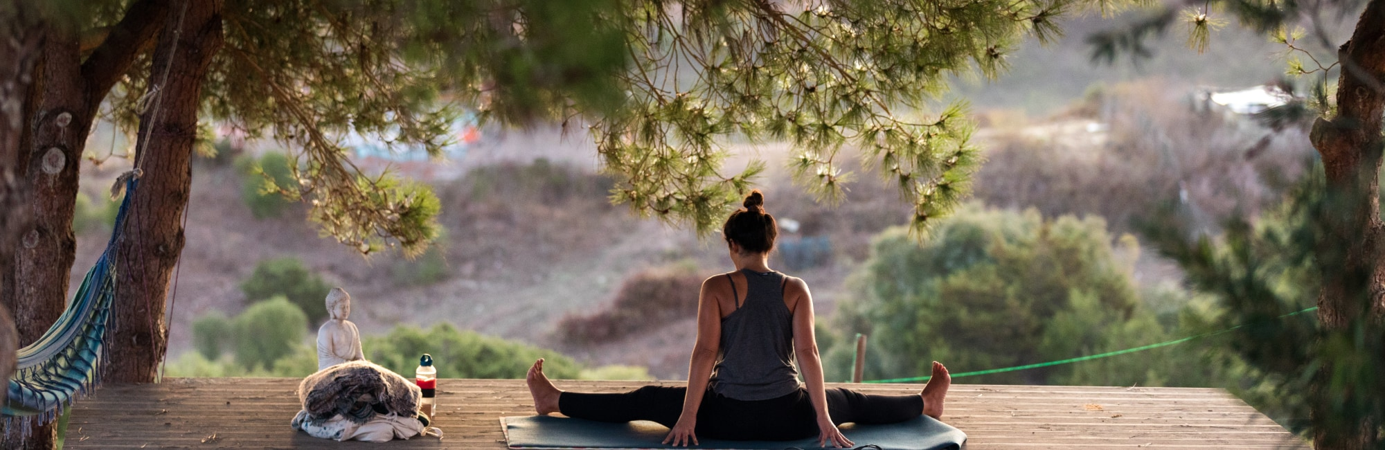 Yoga teacher doing yoga under the trees in south portugal algarve