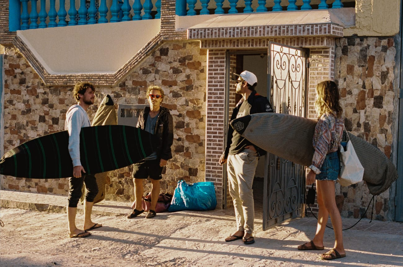 3 surfer boys and one surfer girl with their surfboards in Morocco