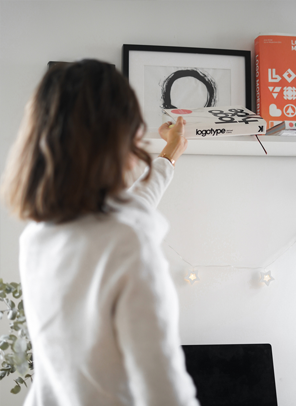 Zoe, the owner of Studio Zo, placing the Logotype book on the shelf in her office.