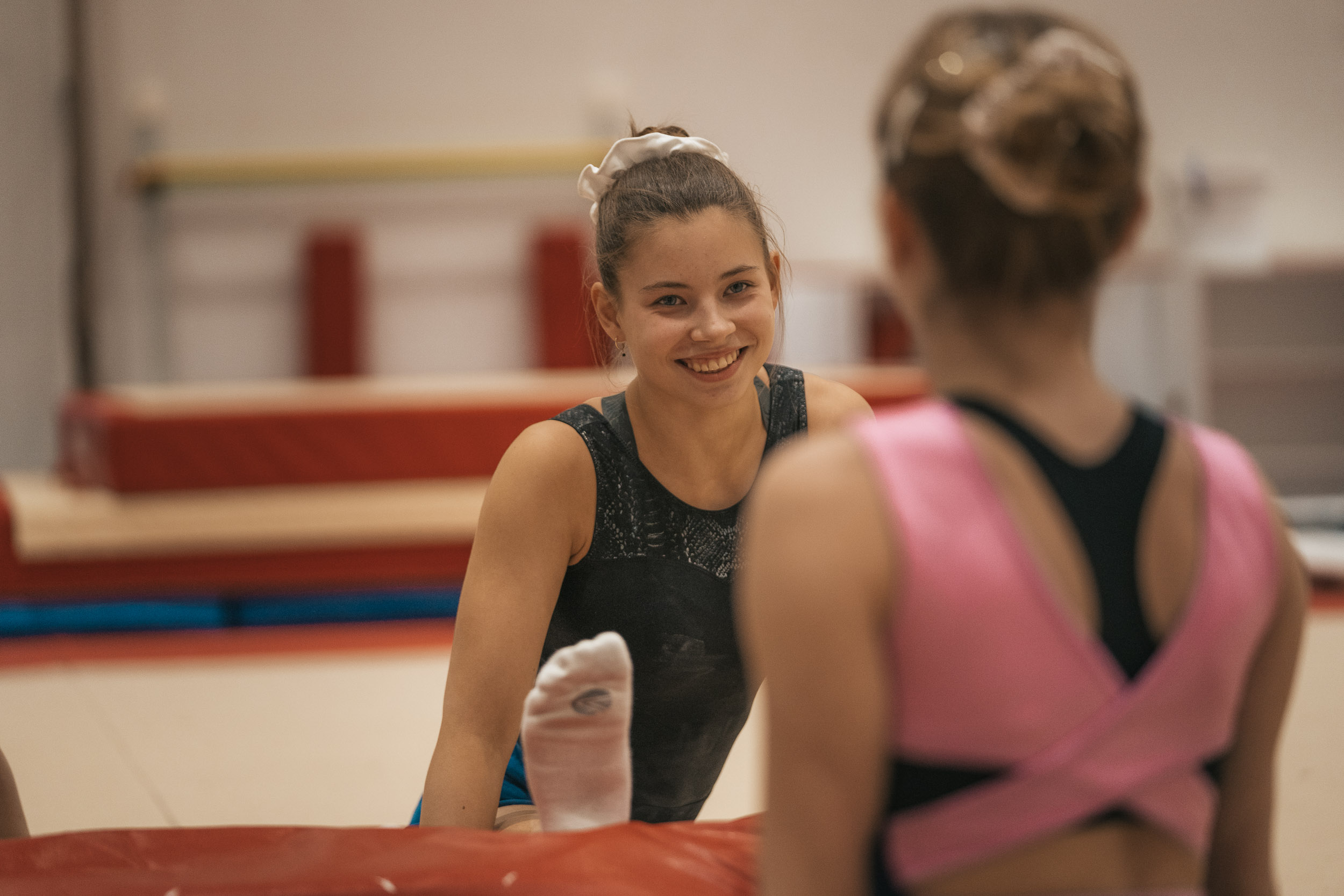A gymnast smiling and stretching