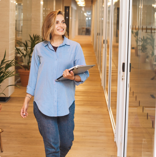 Nasmejna devojka kratke plave kose korača hodnikom kompanije. U levoj ruci nosi laptop i dokumenta.
