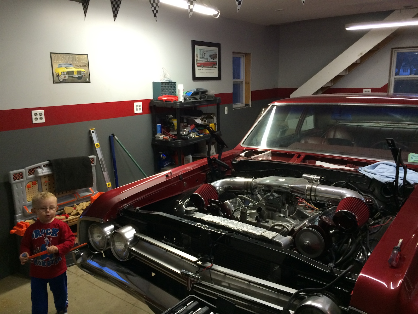 64 oldsmobile f-85 without hood showing engine in garage
