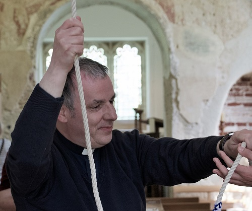 Rector Stephen Thorp hands the bell to a visitor