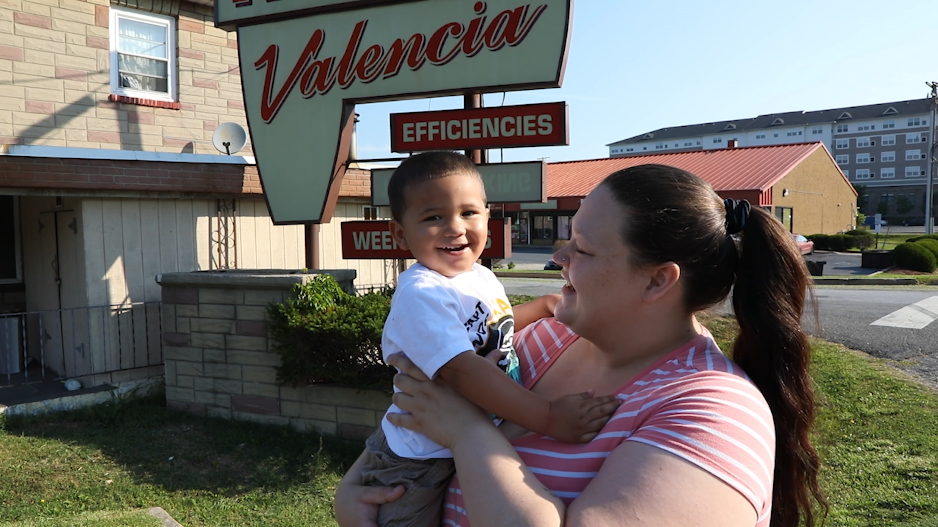 A mother and son outside their residence at a motel.