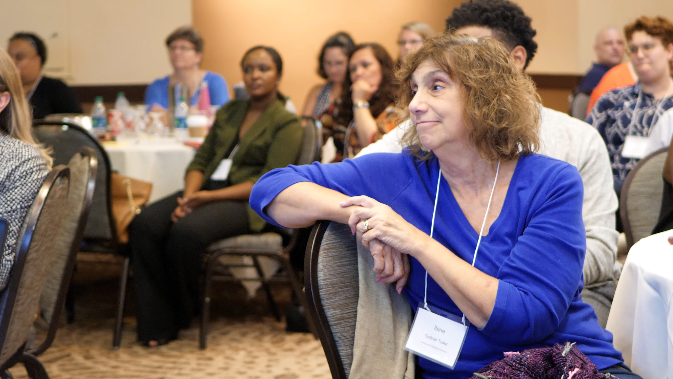 Woman listening to keynote speaker at 2018 conference.