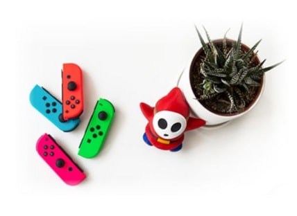 Wii remotes and Nintendo character next to a plant.