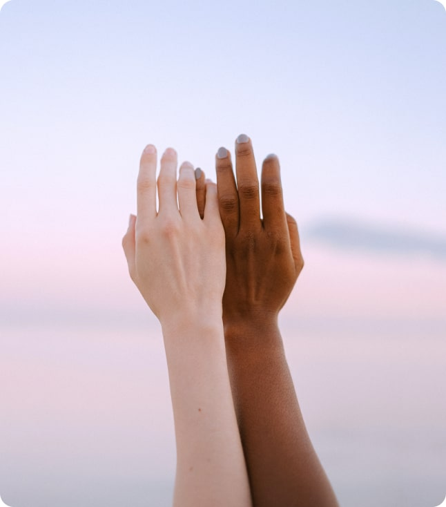 Two hands raised in the sky holding each other.