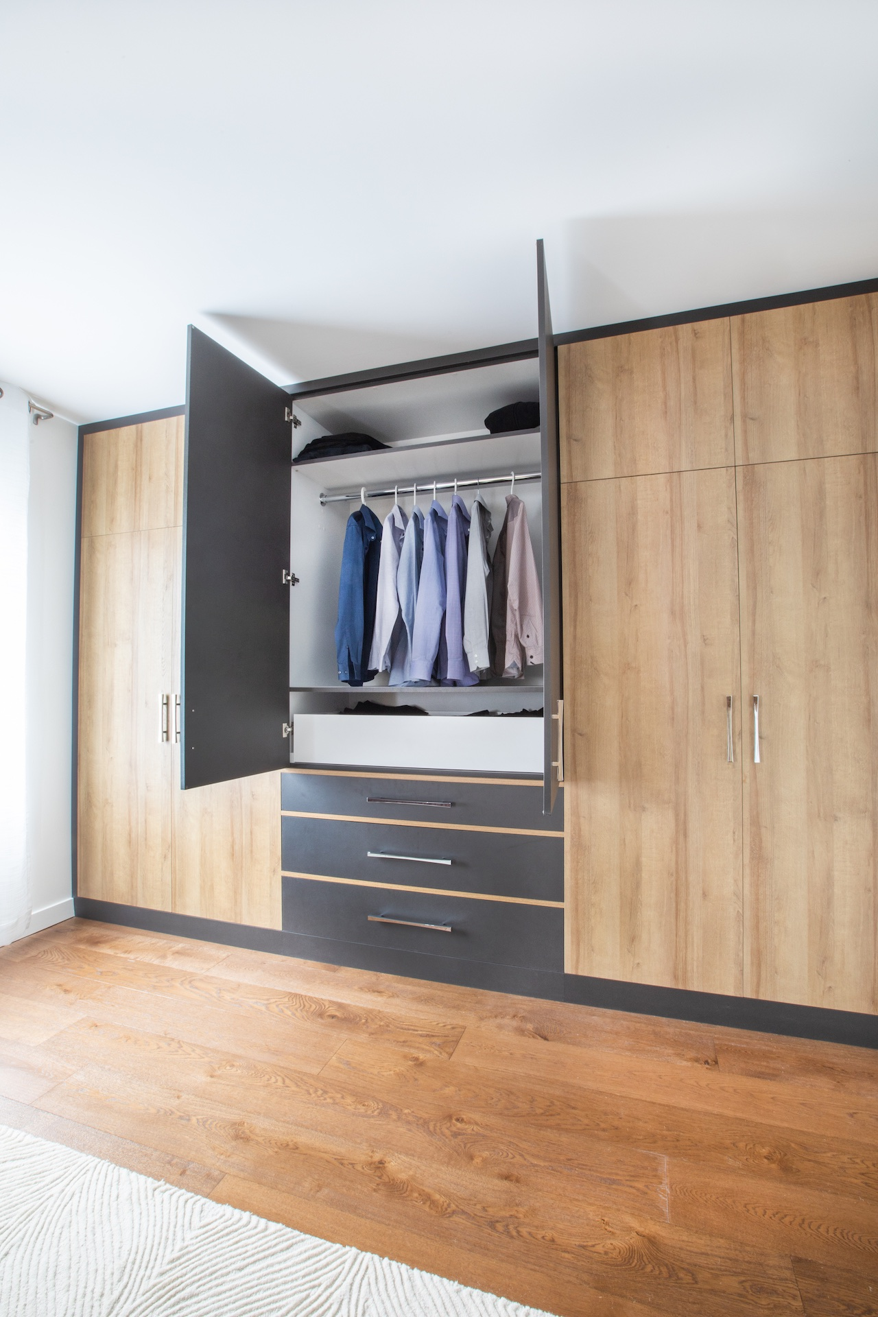 wood wardrobe with open doors and shirts