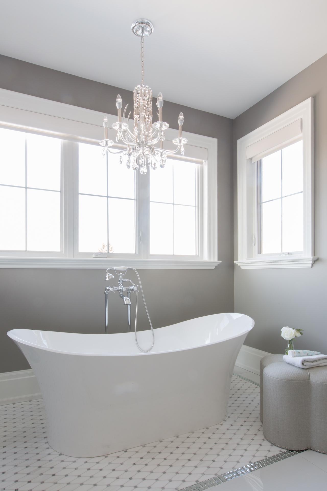 white tub under light with windows