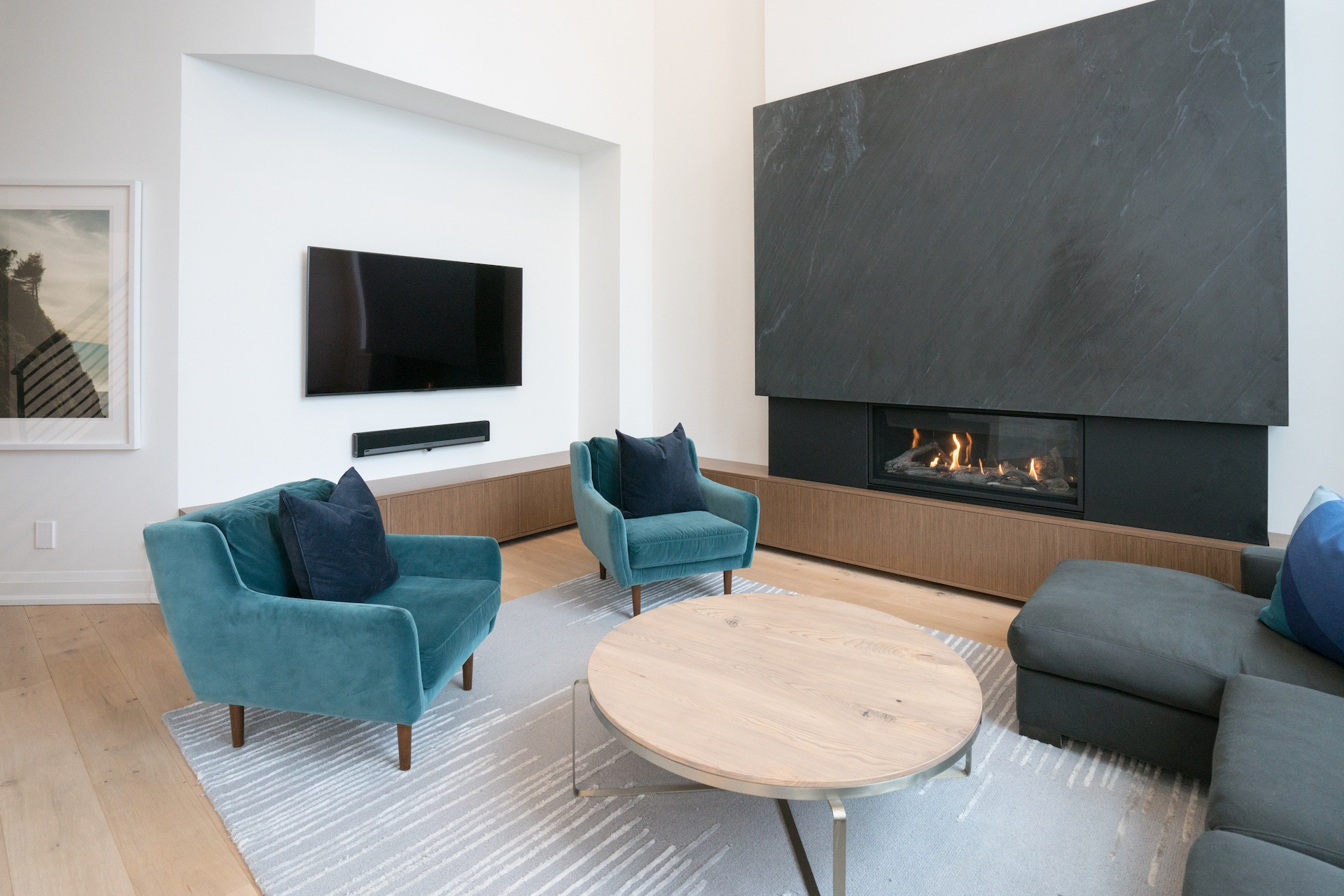 living room with tv on wall and green chairs
