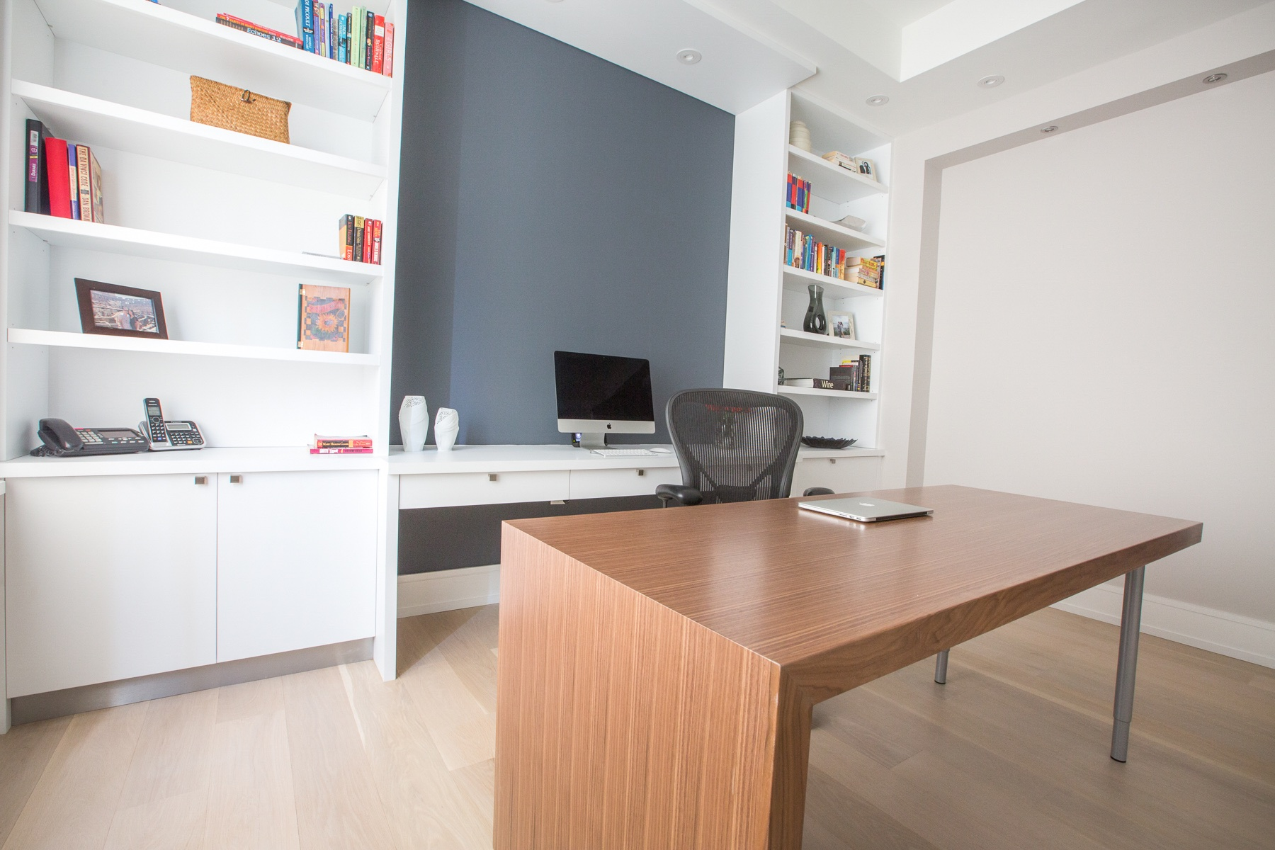natural wood desk with white cabinets