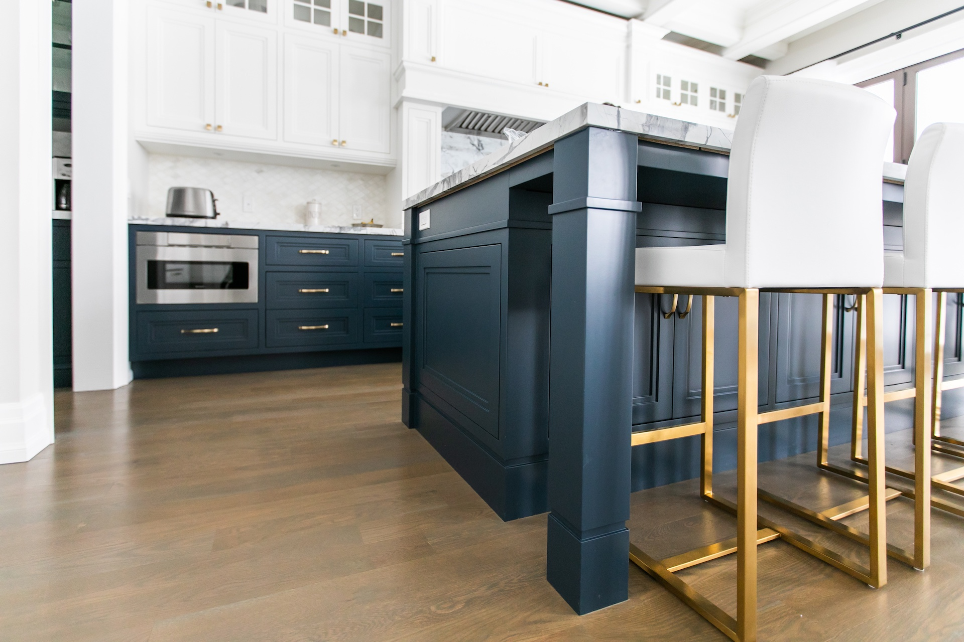 blue kitchen island with white and gold bar stools