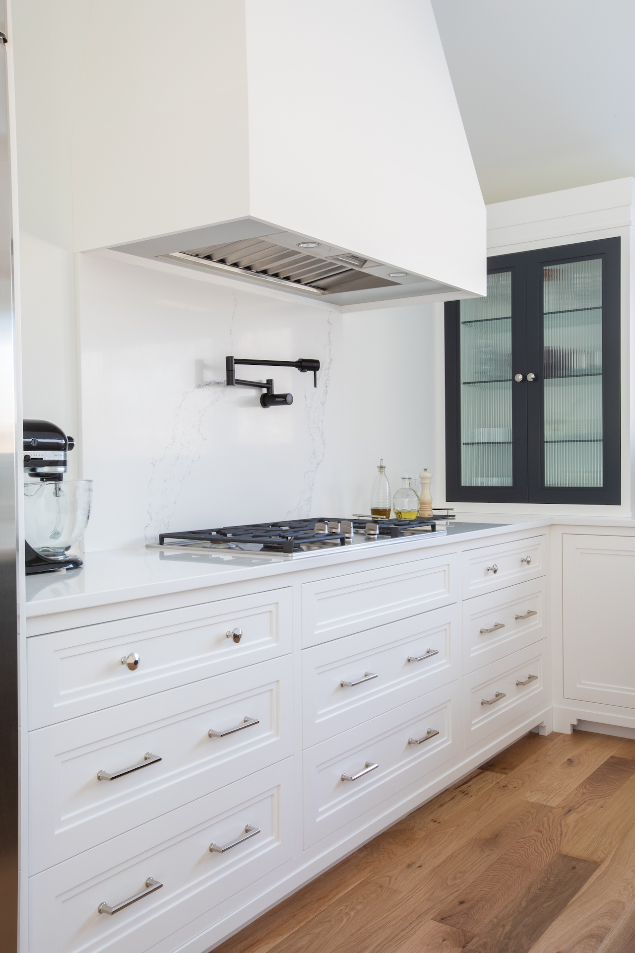 white kitchen cabinets with stove and hood fan