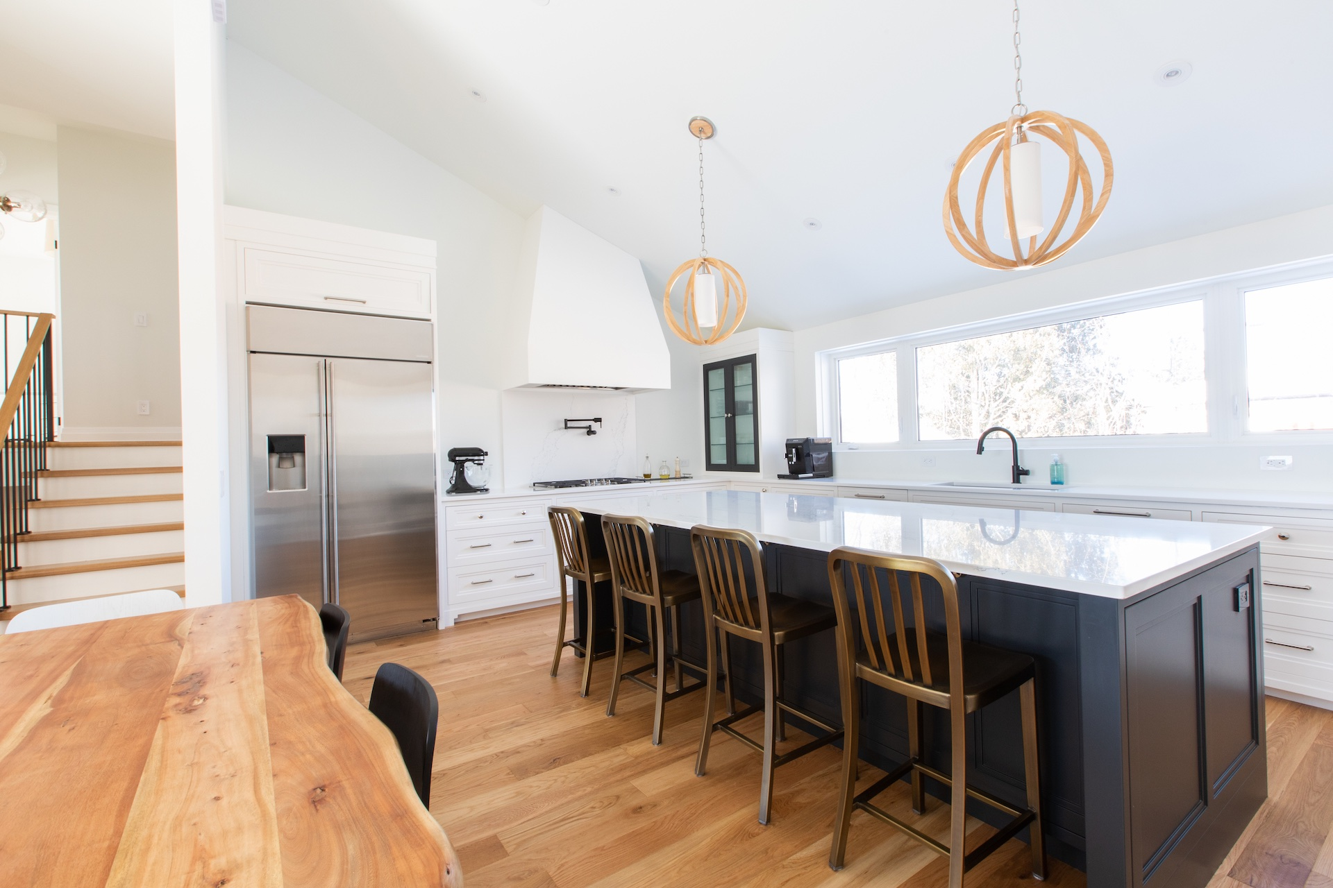 Kitchen with blue island, gold chairs and wood floor