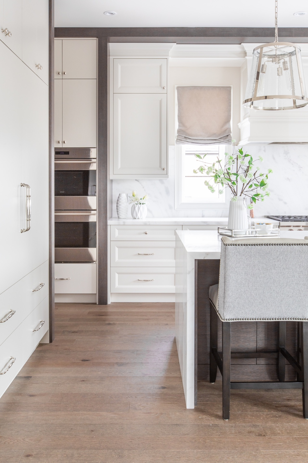 White kitchen with oven in cabinets and bar stool