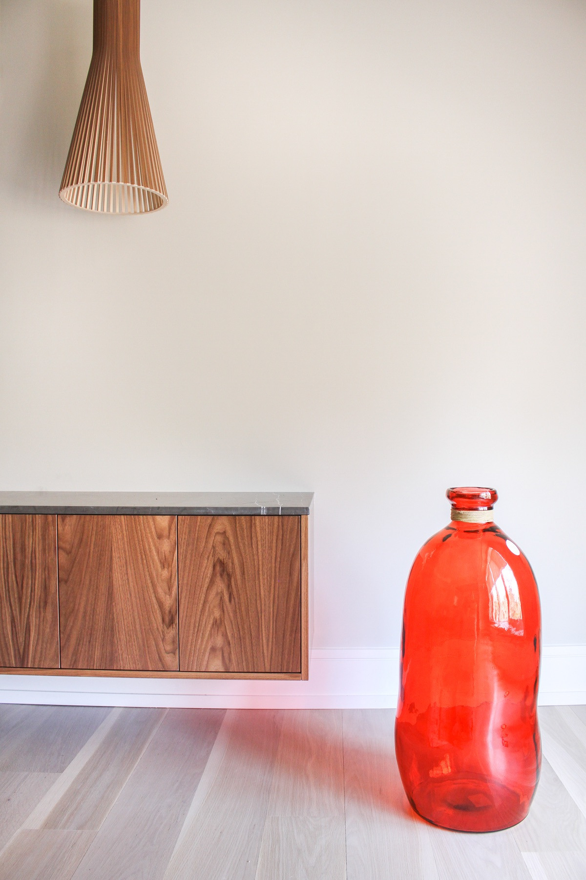 wood cabinet with wood light and red vase
