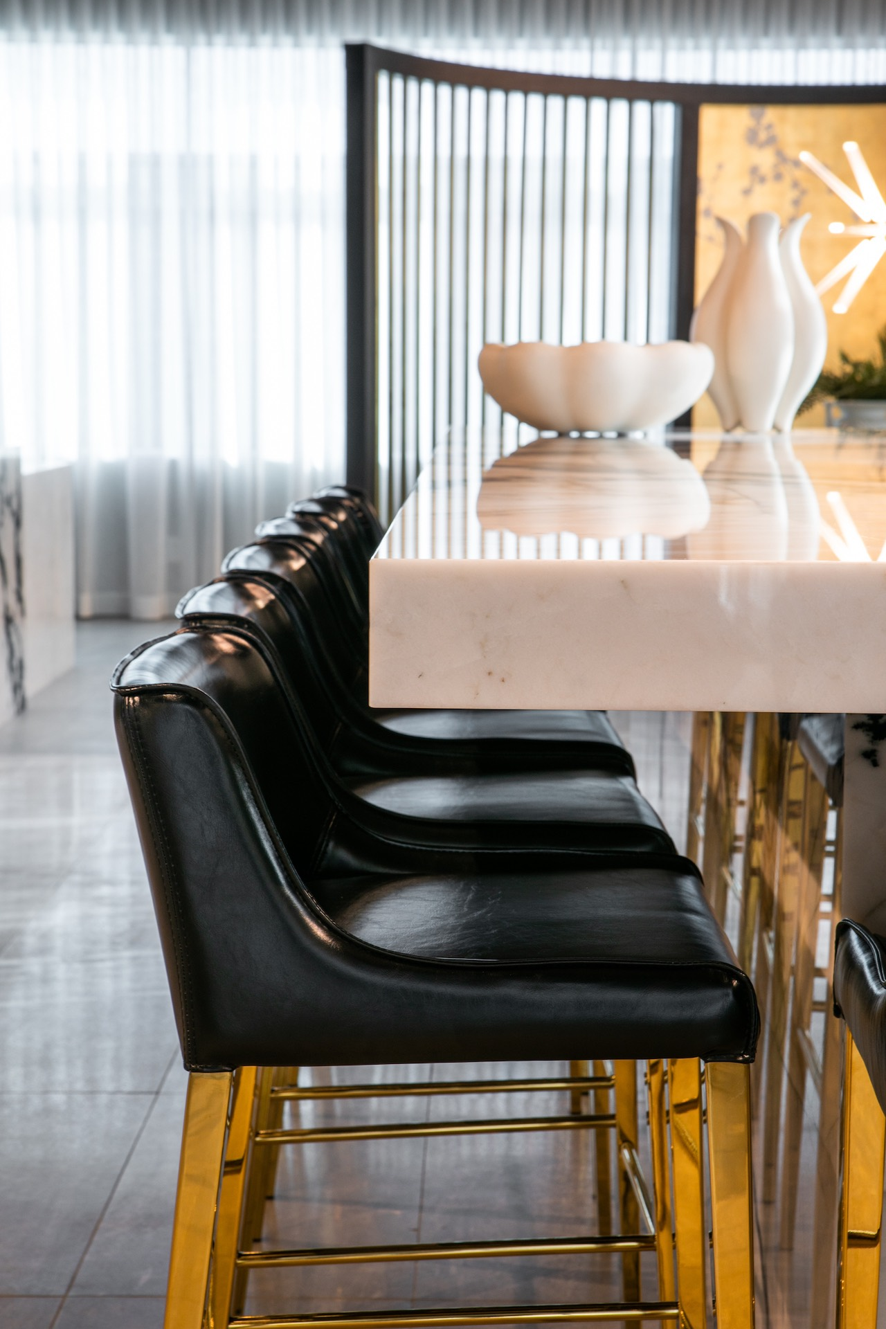 White marble bar with black and gold chairs