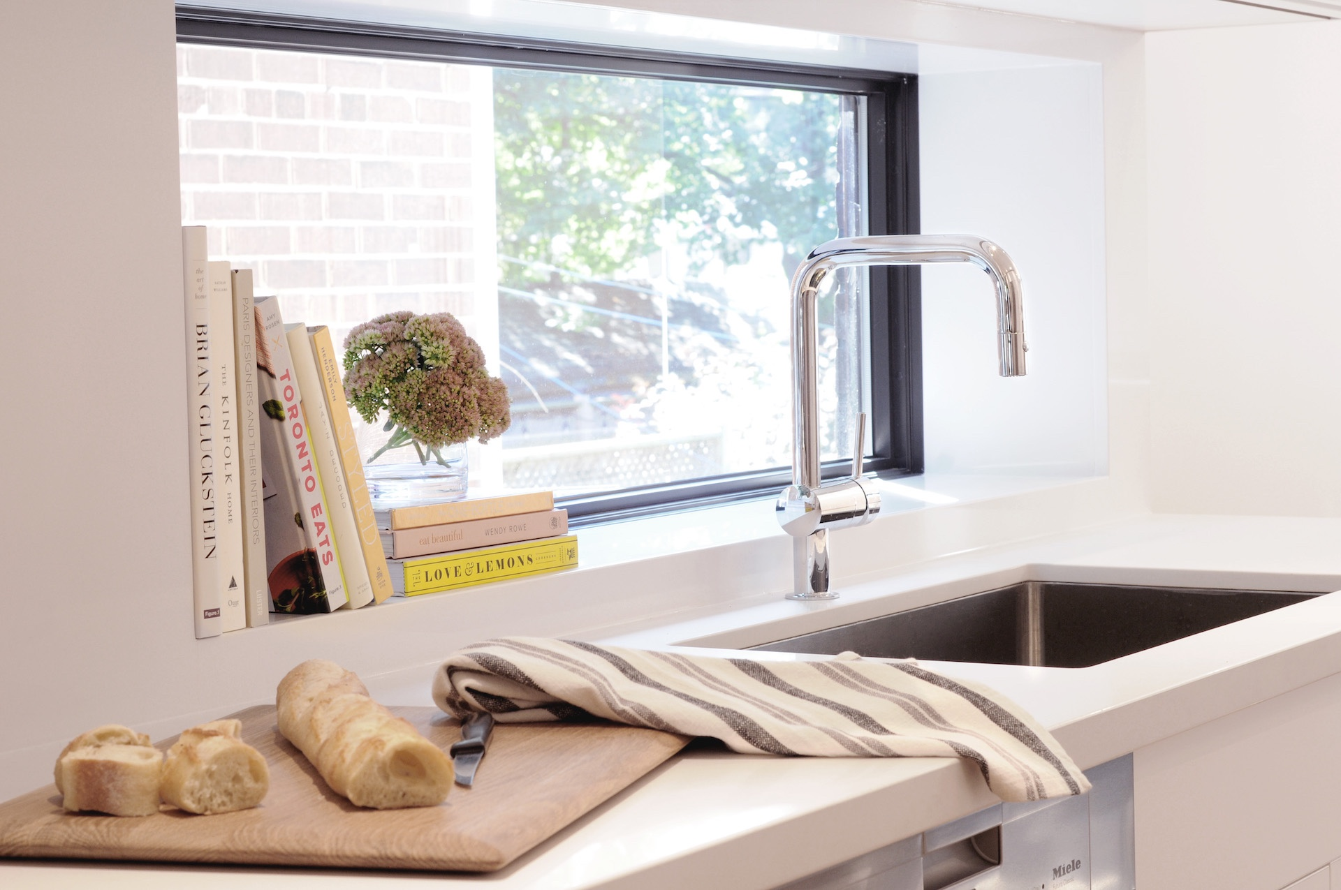 Silver faucet and sink under window