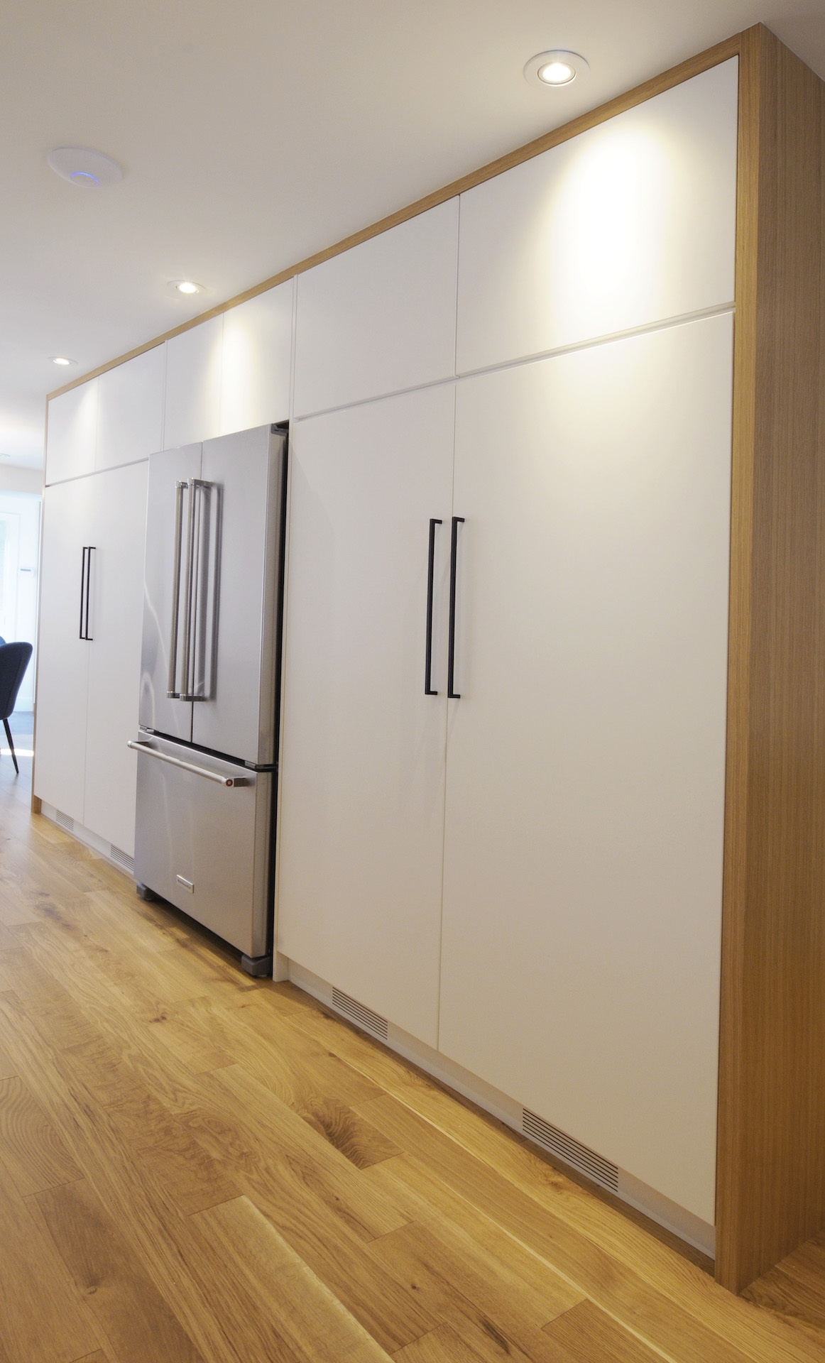 Light wood floor with white cabinets and steel fridge