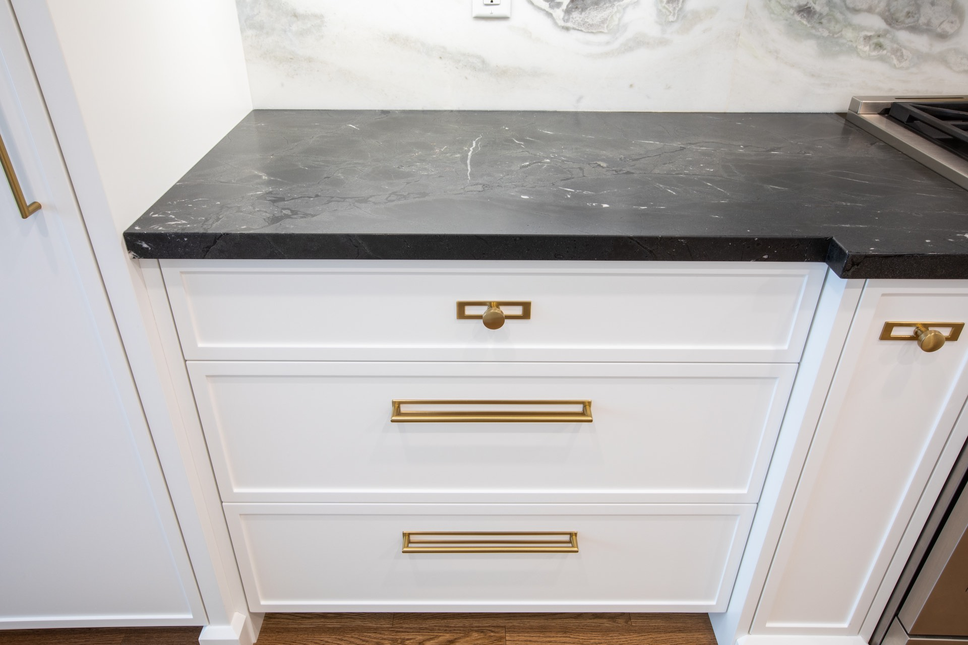 Black marble counter with white kitchen drawers