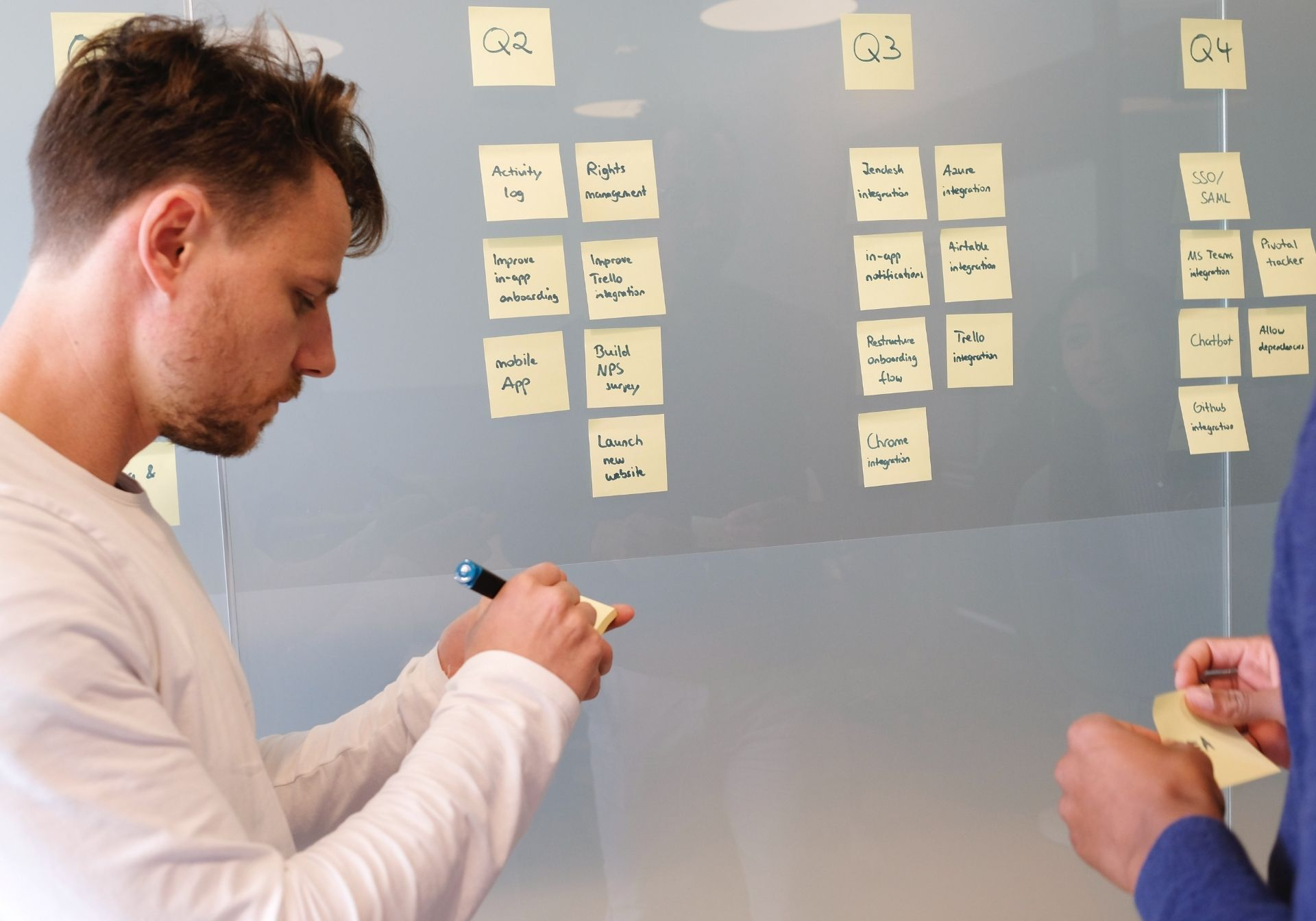 A Man Placing Post-It Notes On A Board