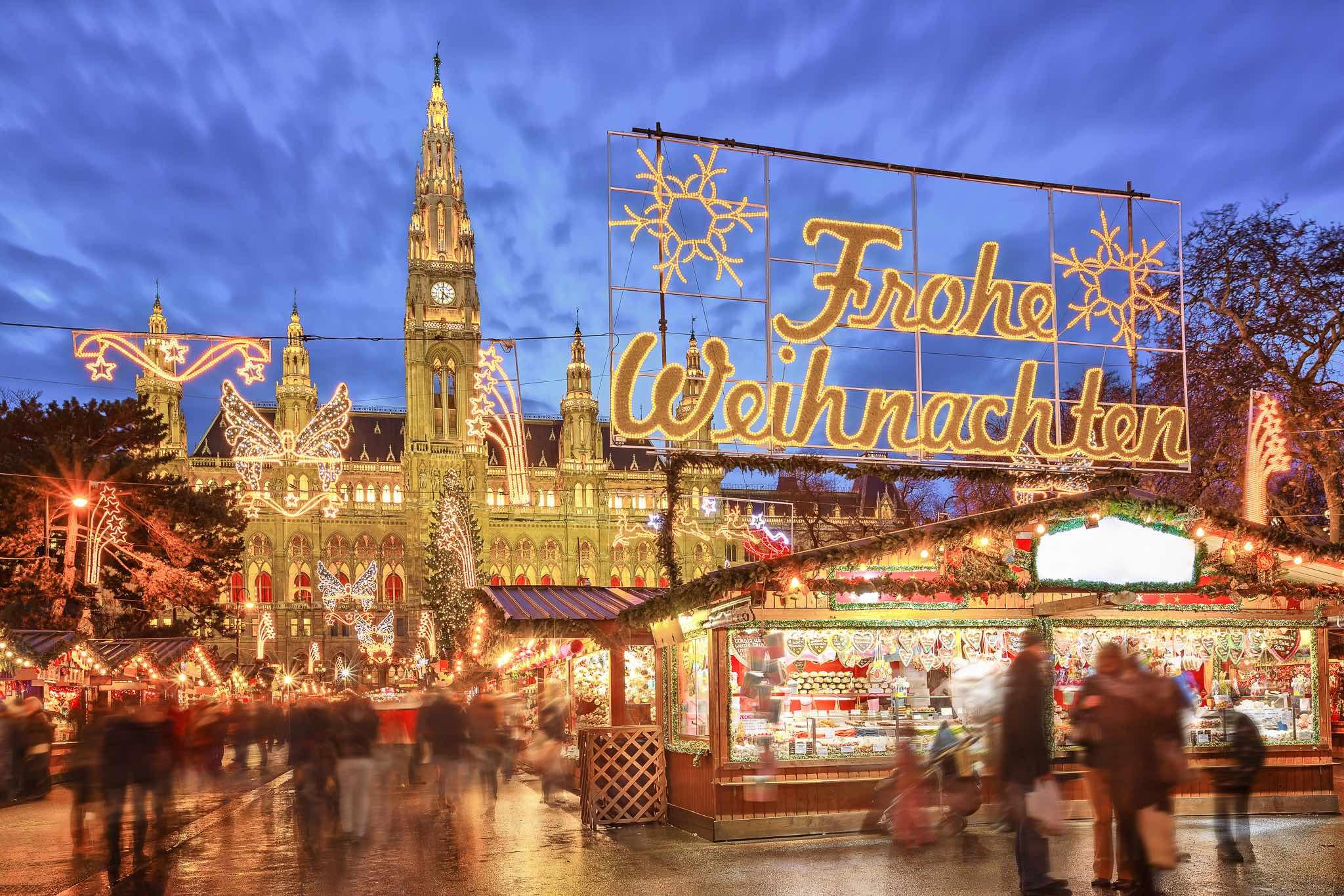 Weihnachtsmarkt vorm Wiener Rathaus mit festlichen Schriftzug Frohe Weihnachten