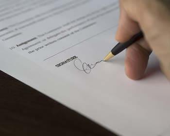 Unterschrift eines Kaufvertrages mit Kugelschreiber und Hand